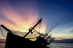 Silhouette of old shipwreck or abandoned shipwreck, Boat capsize. D on the sand beach in beautiful colorful twilight sunset background with plastic tank movement stock photo
