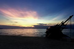 Silhouette of old shipwreck or abandoned shipwreck, Boat capsize. D on the sand beach in beautiful colorful twilight sunset background with plastic tank movement royalty free stock images