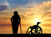 Silhouette of an old woman on crutches on a background of sea sunset and wheelchair. Concept of disability and old age Royalty Free Stock Images
