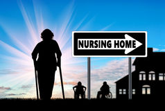 Silhouette of an old woman on crutches near house Stock Photography
