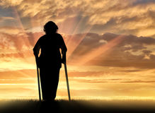 Silhouette of an old woman on crutches outdoors Stock Photo