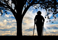 Silhouette of an old woman on crutches resting under a tree. Royalty Free Stock Image