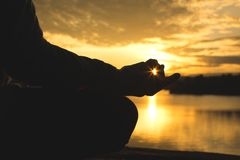 Silhouette of old woman yoga near lake during sunset, Relax time and exercise Stock Photos