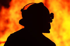 Silhouette one fireman officer front fire flames. A black silhouette image of a single brave rescue firefighter standing in front and watching a bushfire blaze Stock Photo