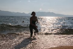 Silhouette of One Girl Running Through the Waves Royalty Free Stock Images