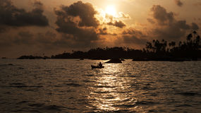 Silhouette of one man rowing a small boat with his paddle on the ocean. Silhouette of one man rowing a small boat with his paddle on the ocean at sunset Stock Images