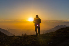 Silhouette of one young man standing at the mountain top Stock Image