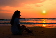Silhouette ot girl sits on the beach. Enjoys a dec Royalty Free Stock Photo