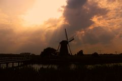 Silhouette of windmill under sunset stock image