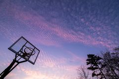 Silhouette of outdoor basketball goal with clear backboard and s. Unset in the background visible through backboard stock photos