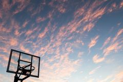 Silhouette of outdoor basketball goal with clear backboard and s. Unset in the background visible through backboard stock photo