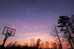 Silhouette of outdoor basketball goal with clear backboard and s. Unset in the background visible through backboard stock image