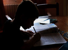 Silhouette over bright window light background of Children on his school homework Royalty Free Stock Photography