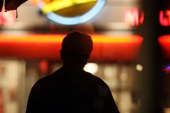 Silhouette over neon lights. Black male silhouette over blurred neon lights background in night city Royalty Free Stock Photography
