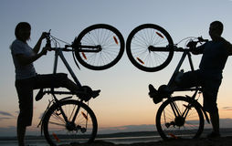 Silhouette of a pair. Of lifting bikes Stock Photos