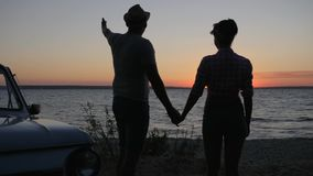 Silhouette of pair That holding hands and Looks in evening sundown Outdoors, romantic Trip of Lovers to seafront. Silhouette pair That holding hands and Looks in stock footage