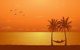 Silhouette palm tree with hammock on beach under sunset sky background Stock Photography