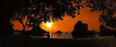 Silhouette of Panoramic landscape of Ang Thong archipelago island in Thailand with a girl sitting on a swing or cradle on the. Beach at sunset stock images