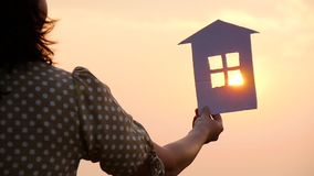 Silhouette of a paper house in hands at sunset in the sun. Close up stock video
