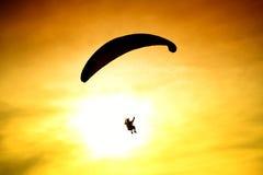 Silhouette of parachute on sunset Stock Photos