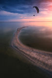 Silhouette of paraglide flying above the sea. Against bright colorful sunset Stock Image