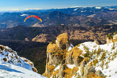 Silhouette of paraglide flying over the high mountains,Ceahlau,Romania Stock Photography
