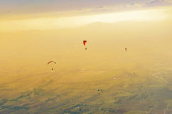 Silhouette of paraglide flying over the high mountains. In a light of sunrise Stock Photography