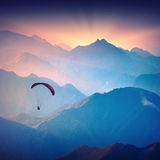 Silhouette of paraglide. Flying over the high mountains in a light of sunrise. Ukrainian Carpathian valley Stock Photo