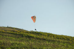 Silhouette of paraglide flying in the sky with clouds in a light of sunrise. Ukrainian Carpathian valley Royalty Free Stock Photography