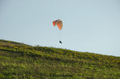 Silhouette of paraglide flying in the sky with clouds in a light of sunrise. Ukrainian Carpathian valley Stock Photos