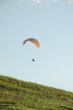 Silhouette of paraglide flying in the sky with clouds in a light of sunrise. Ukrainian Carpathian valley Stock Photography