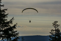 Silhouette of a paraglider against the background of the evening sky. Tandem paragliding flight with blue glide and nice fluffy thermal clouds in background Royalty Free Stock Images