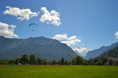 Silhouette of a paraglider over the mountains covered with forest. royalty free stock image