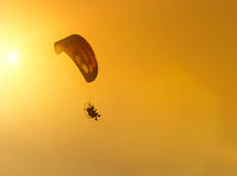 Silhouette paramotor flying on sunset Stock Images