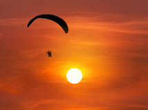 Silhouette paramotor flying with on sunset Royalty Free Stock Photography