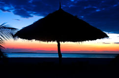 Silhouette of Parasol on a beach over Sunset Royalty Free Stock Image
