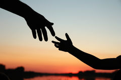 Silhouette parent holds the hand of achild Royalty Free Stock Images