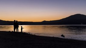 Silhouette of Family at a Lake stock image
