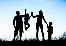 Silhouette of parents and kid having fun spending time.  Stock Photos
