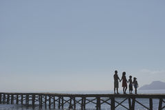 Silhouette Parents And Kids Holding Hands On Jetty Royalty Free Stock Photos
