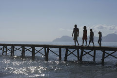 Silhouette Parents And Kids Walking On Jetty Royalty Free Stock Photo