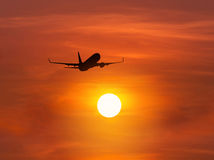 Silhouette passenger airplane flying above the sun during sunset. Silhouette passenger airplane flying away in to sky high altitude above the sun during sunset Stock Photo