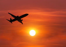 Silhouette passenger airplane flying above the sun during sunset. Silhouette passenger airplane flying away in to sky high altitude above the sun during sunset Royalty Free Stock Images