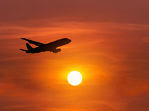 Silhouette passenger airplane flying away in to sky on sunset Royalty Free Stock Photos