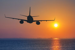 Silhouette of passenger. Airplane flying on sunset Stock Image