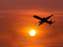 Silhouette passenger airplane flying on sunset. Silhouette passenger airplane flying away in to sky high altitude on sunset Stock Photos