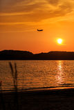 Silhouette of Passenger Airplane Landing at sunset. Above the sea Royalty Free Stock Photography