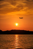 Silhouette of Passenger Airplane Landing at sunset. Above the sea Stock Image