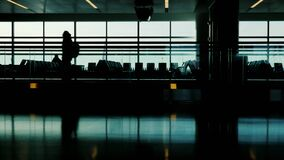 Silhouette of a passenger hurrying on his flight. Against the background of a large window, behind which is seen a. Flying aircraft. Do not miss your flight stock footage