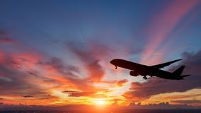 The silhouette of a passenger plane flying in sunset. Stock Images